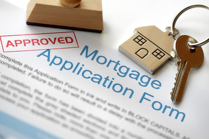 an approved mortgage application form and a key