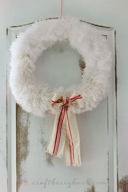White fuzzy wreath with bow on distressed door