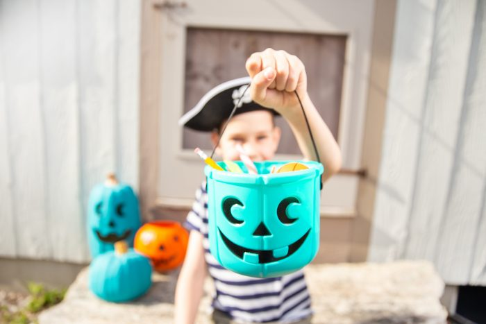 A kid in a pirate hat holding up his blue halloween candy bucket