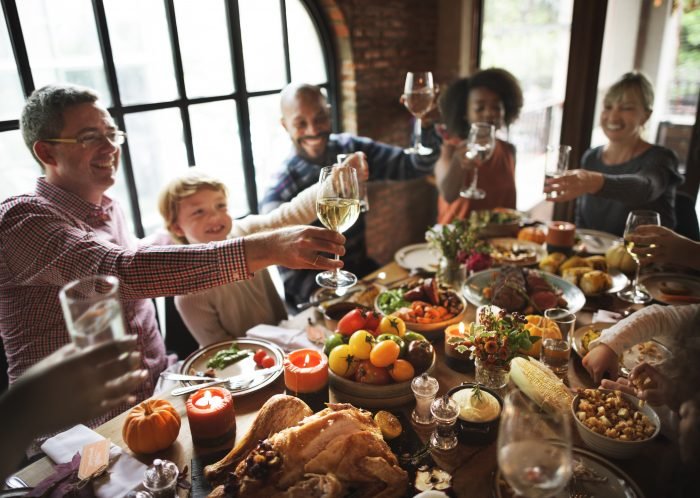 Large group of people of all race cheersing during a Thanksgiving meal