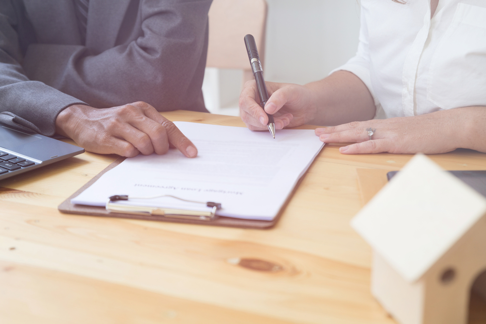 A woman signing a piece of paper on a clipboard