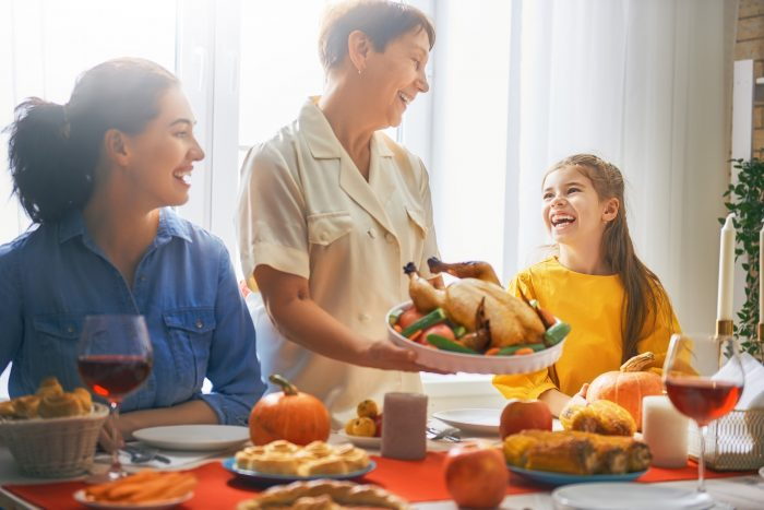 A woman, grandmother and child laughing while holding a turkey